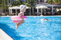 Little girl at swimming pool jumping to the Royalty Free Stock Images