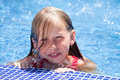 Little girl in swimming pool smiling face of caucasian at board on blue water background Stock Image