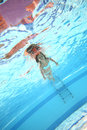 Little girl swimming underwater with open eyes in the pool bottom view Royalty Free Stock Photos