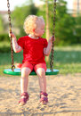 Little girl on a swing in the park Stock Image