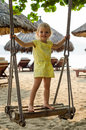 Little girl swinging with the beach in the background Royalty Free Stock Photo
