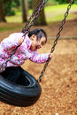 Little girl swinging a having a great time on a swing in a playground Royalty Free Stock Images
