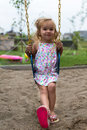 Little girl swinging after a meal posing on the swing in very natural way Stock Photography