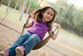 Little girl swinging at the playground Stock Photo