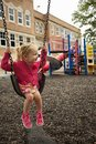 Little girl swinging young looking to the side while she swings Royalty Free Stock Photo