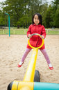 A little girl swings in red coat Royalty Free Stock Images