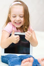 Little girl with tablet computer happy using shows her thumb up indoors Stock Images