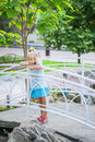 Little girl talking stands on bridge and sad against green of park in summer Stock Photos