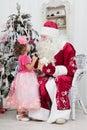 Little girl talks to santa claus near a christmas fir tree Stock Photography