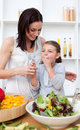 Little girl tasting salad with her mother Stock Images