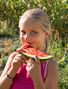 Little girl tasting watermelon on nature background Royalty Free Stock Images