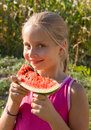 Little girl tasting watermelon on nature background Stock Image