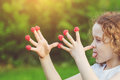 Little girl teasing is putting fingers to nose with raspberry f focus on Royalty Free Stock Photos