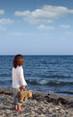 Little girl with teddy bear on beach summer season Stock Photography