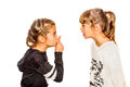 Little girl telling her sister to shut up with her finger on the mouth a gesture of silence closeup isolated white background Royalty Free Stock Image