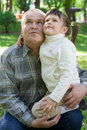 Little girl tenderly embraces grandfather and sits