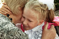 Little girl tenderly embraces grandmother in day back to school