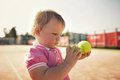Little girl with tennis ball funny Royalty Free Stock Photo