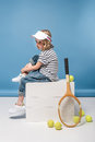 Little girl with tennis raquet and balls sitting on white boxes Royalty Free Stock Photo