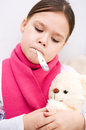 Little girl with thermometer in her mouth is laying on sofa Royalty Free Stock Photo