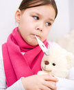 Little girl with thermometer in her mouth is laying on sofa Stock Images