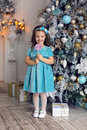 Little girl three years in a blue dress licks Royalty Free Stock Photo