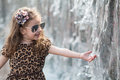Little girl touching hand waterfall in a leopard dress Royalty Free Stock Photography
