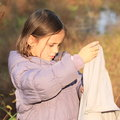 Little girl with towel kid young in lila jacket drying hands outside on autumn Stock Image