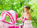 Little girl with toy carriage Royalty Free Stock Photo