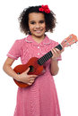 A little girl with a toy guitar pretty kid loves music holding in hand Stock Photography