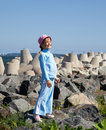 Little girl in tracksuit stand on rocks Stock Photo