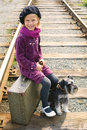 Little girl traveling with a dog sitting on suitcase waiting for train Royalty Free Stock Image