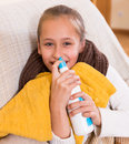 Little girl treating for rhinitis with sea water and smiling Stock Photos