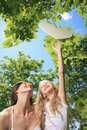 A little girl try to catch heart on a tree with is mother Royalty Free Stock Image