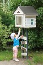 Little girl trying to get a book out of a community public street library. Bookcrossing. Royalty Free Stock Photo