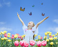 Little girl in tulips with hands up and butterfly Royalty Free Stock Photo