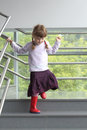 Little girl with two pigtails holding railing down stairs Stock Photography