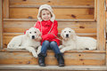 A little girl with two puppy golden retriever portrait of beautiful her dogs labrador child puppies of sitting on stair Royalty Free Stock Photos