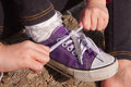 Little girl tying shoelaces close up landscape hoizontal format shot of girls hands lacing up on purple sneakers Royalty Free Stock Photography