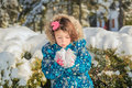 Little girl tying to blow a snow from her hands child in winter garden holding in Royalty Free Stock Images