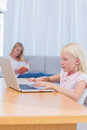 Little girl typing on laptop in the living room while her mother is reading couch Royalty Free Stock Photography