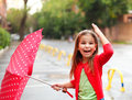 Little girl under the rain child with polka dots umbrella wearing red boots jumping into a puddle Royalty Free Stock Images
