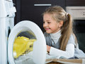 Little girl unloading washing machine and smiling Royalty Free Stock Photo