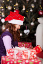 Little girl unwrapping christmas gifts in front of the decorated tree amongst a pile of giftwrapped boxes wearing a red Royalty Free Stock Image