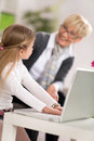 Little girl using laptop with grandmother at home Royalty Free Stock Photos