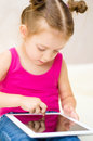 Little girl using tablet computer cute at home Stock Photos