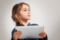 Little girl using a tablet device on grey background Royalty Free Stock Images