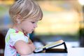 Little girl using tablet pc at home happy child adorable blonde toddler enjoying modern generation technologies playing indoors Stock Photo