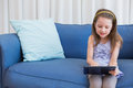 Little girl using tablet pc at home in the living room Stock Photography