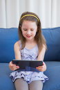 Little girl using tablet pc at home in the living room Stock Photo